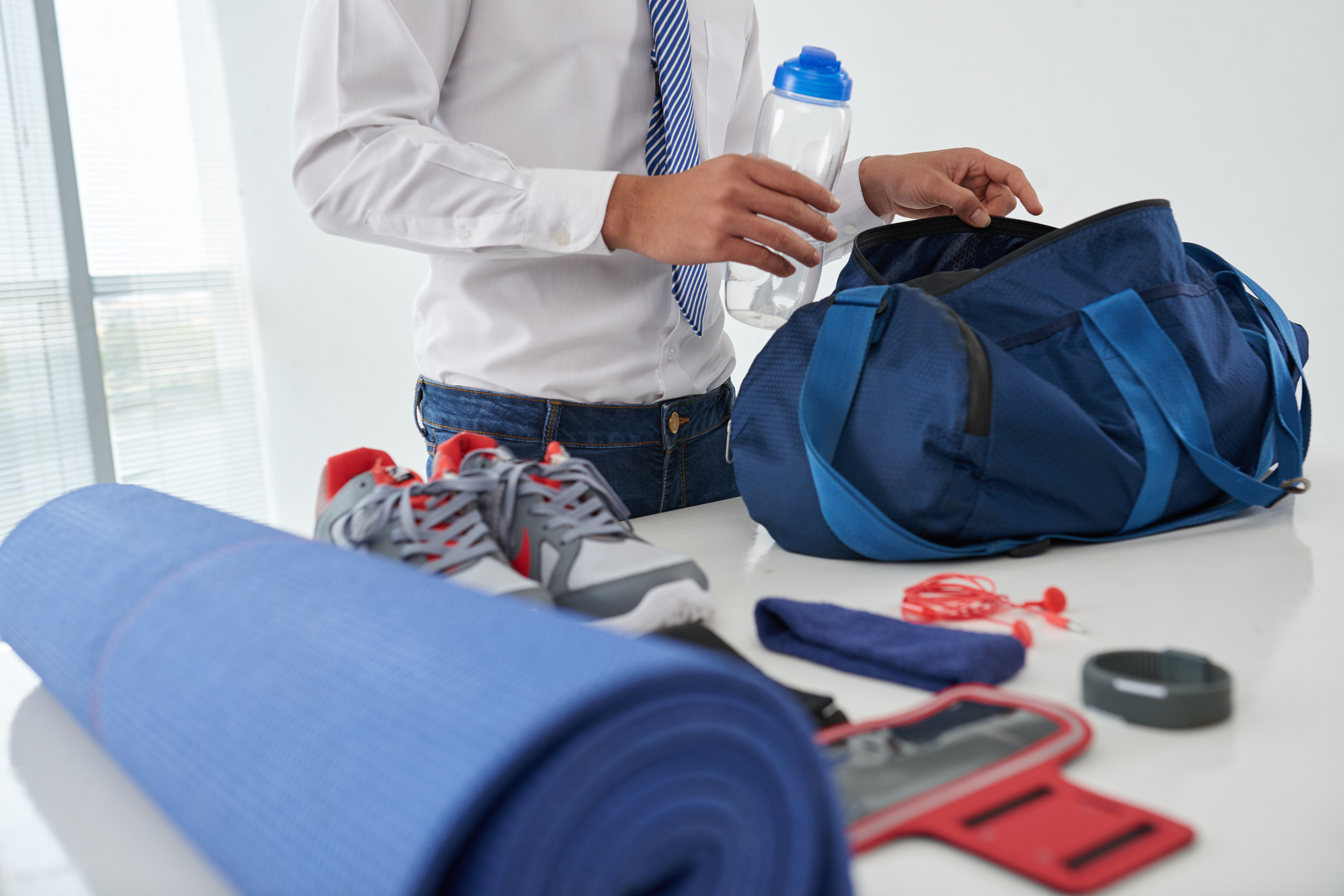 Man putting workout gear into gym bag at work