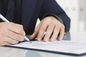 Picture of man's hands signing forms