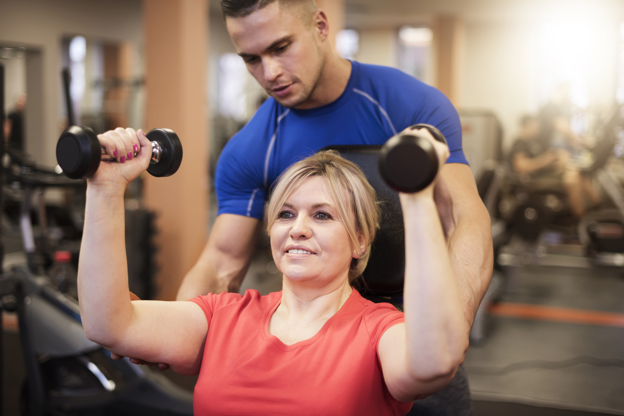 Woman weight lifting with personal trainer