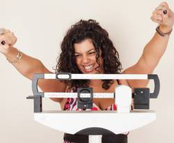 Woman on weight loss scale - happy because of weight loss
